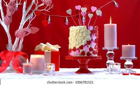 Beautiful St Valentines Day party table with showstopper red, white and pink hearts double layer cake, with white chocolate frosting