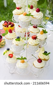 Beautiful stand with mascarpone cupcakes and berries on top on a decorated table set outdoors