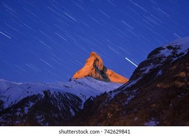 Beautiful star trails over the famous mountain Matterhorn at sunrise tine in winter, Zermatt, Switzerland.