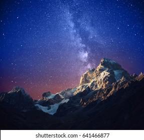Beautiful starry night and Ushba mountain. Stylized image. Svaneti, Georgia, Europe.