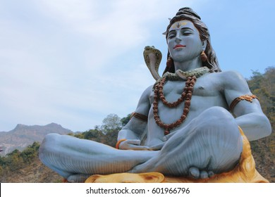Beautiful statue of meditating Shiva. Lord Shiva sits near the Ganges River at the foot of the Himalayas in Rishikesh, India. Yoga and meditation concept.