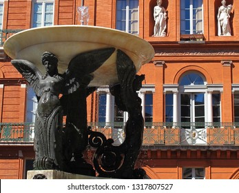 The beautiful Statue, Trinity fountain in the historical district of Toulouse, with red brick building in background, France.