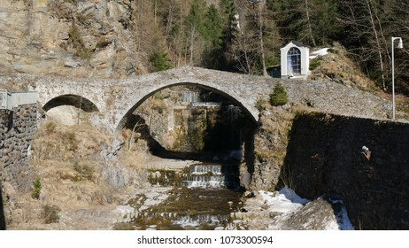a beautiful stone bridge over a stream in the  alpine village of Montedolcino, Lombardy, Italy