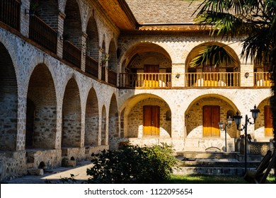 beautiful stone building with arches, European architecture and green palm trees