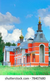 Beautiful stone church with red plaster and golden domes against the dark blue sky with clouds.