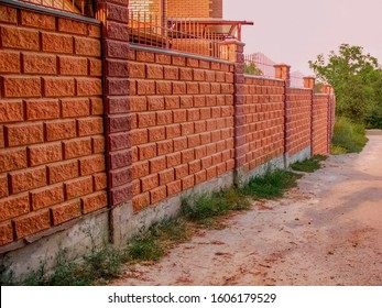 Beautiful stone fence made of blocks. Fence of foam concrete blocks to fence the territory.  Brickwork. Stone wall cladding. A fence around the territory of a private house made of concrete blocks.