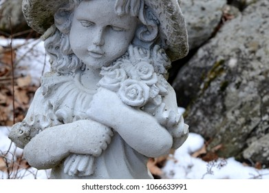 A beautiful stone girl statue graces the garden around her.
