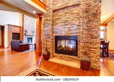 Beautiful stone wall with built-in fake fireplace. Two vases with dry branches complete the wall look