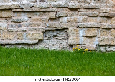 Beautiful stone wall of castle. Green grass in foreground.