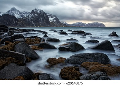 Beautiful stones on a background of snow-capped mountains. Cloudy Nordic day. Lofoten islands, Norway
