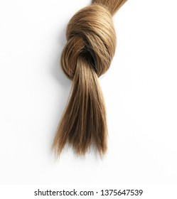 Beautiful strand of brown hair tied in knot on white background, top view. Hairdresser service