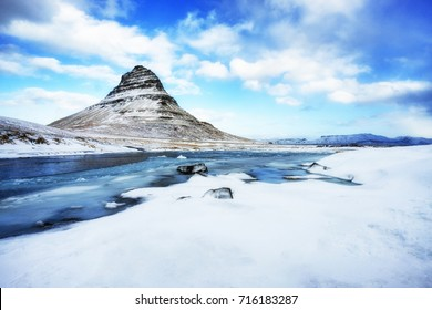 A beautiful stream and Kirjufell mountain covered with snow during winter in Iceland.