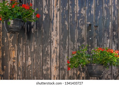 Beautiful street decorated with flowers in France. Summer flowers decoration on dark paint wood background.