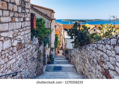 Beautiful street with flowers in the Hvar town, Hvar island, Dalmatia, Croatia. Old Mediterranean street, Hvar town. Old Adriatic town Hvar. Medieval street. Popular touristic destination of Croatia.
