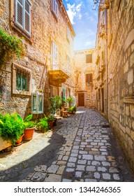 Beautiful street with flowers in the Hvar town, Hvar island, Dalmatia, Croatia. Old Mediterranean street, Hvar town. Old Adriatic town Hvar. Medieval street. Popular touristic destination of Croatia.