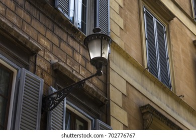 Beautiful street lantern of wrought iron and a glass lampshade on the facade of an old building, Rome, Italy