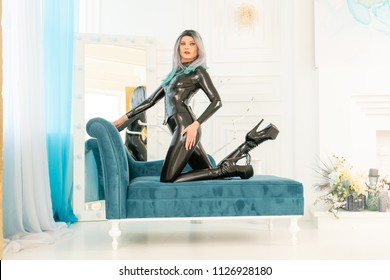 beautiful strict mistress is lying in her white room on the couch in bdsm black latex suit