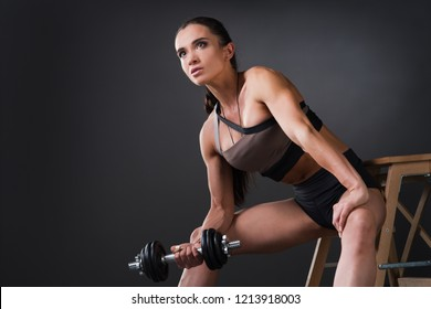 Beautiful strong female athlete bodybuilder with big muscles doing strength exercises with dumbbells on a dark background