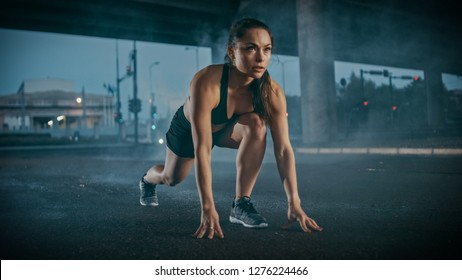 Beautiful Strong Fitness Girl in Black Athletic Top and Shorts Ready for Sprinting. She is Training in an Urban Environment Under a Bridge with Cars in the Background.