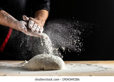 Beautiful and strong men's hands knead the dough make bread, pasta or pizza. Powdery flour flying into air. chef hands with flour in a freeze motion of a cloud of flour midair.