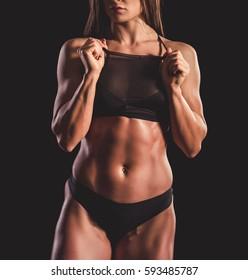 Beautiful strong muscular woman in black underwear on dark background