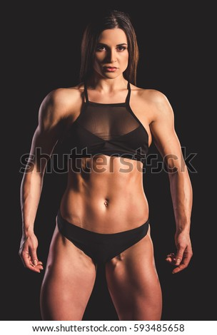 Beautiful Strong Muscular Woman In Black Underwear On Dark Background