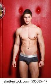 Beautiful strong muscular young man standing in his underwear with a naked torso behind him red background