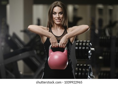Beautiful strong sexy athletic muscular young caucasian fitness girl workout training in the gym on diet pumping up abs muscles and posing bodybuilding health care and fitness concept