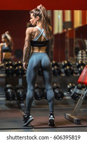 Beautiful strong woman in the gym - latissimus, back and shoulders exercises.