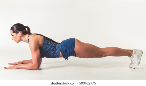 Beautiful strong woman in sportswear is doing plank exercise, on light background