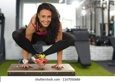 Beautiful strong woman wearing in sportswear, doing yoga exercise on black box, balance handstand pose exercises with crossed legs in gym. Girl smiling and looking at camera. Concept of yoga health.