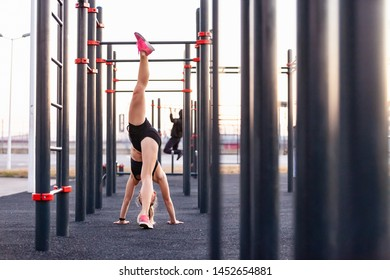 Beautiful strong young female athlete doing handstand on the street of the playground sunny warm summer day. Concept of good physical shape and healthy lifestyle