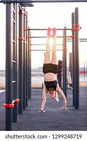 Beautiful strong young female instructor in the gym doing handstand on the street of the playground sunny warm summer day. Concept of good physical shape and healthy lifestyle