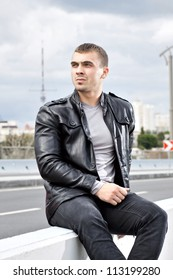 Beautiful strong young man sitting alongside a road