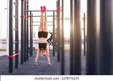 Beautiful strong young woman athlete doing handstand on the street of the playground sunny warm summer day. Concept of good physical shape and healthy lifestyle
