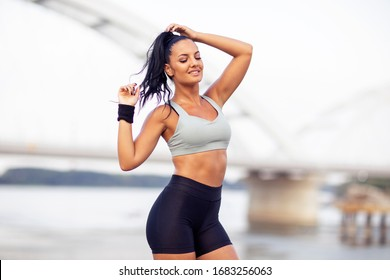 Beautiful strong young woman posing after jogging