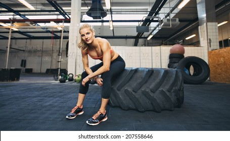 Beautiful and strong young woman sitting on a big tire after her exercise. Woman taking break after crossfit workout at gym.