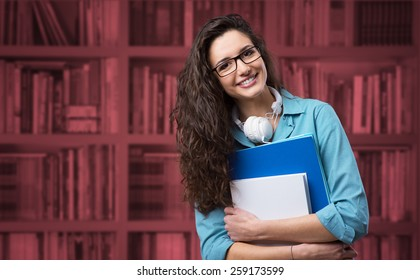 Beautiful student girl posing with books and smiling at camera