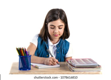 A beautiful student girl sits at the desk and writes the letter. White background.