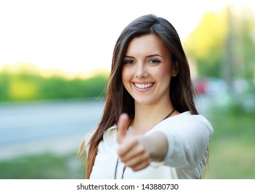 Beautiful student girl in white blouse lifts thumb upwards, against green of summer park.