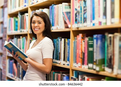 Beautiful student holding a book in a library