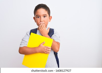 Beautiful student kid boy wearing backpack holding book over isolated white background cover mouth with hand shocked with shame for mistake, expression of fear, scared in silence, secret concept