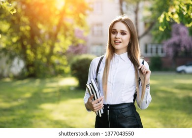 Beautiful student near the university with books in her hand. Before the entry. Freshmen prepare for exams. Spring outside