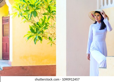 a beautiful student women with a white Vietnam culture traditional dress walking at the staircase in the ancient city