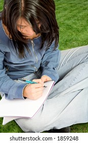 beautiful student working outdoors in a park