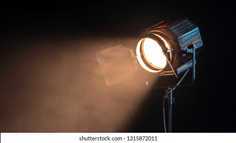Beautiful studio light for a movie and TV show on a dark background with smoke. A ray of light penetrates the smoke and darkness. Professional light for the production of cinema.