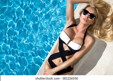 Beautiful stunning  sexy blonde woman  in sunglasses and elegant clothes and bikini  around the pool with amazing views of the sea and the Santorini Island
