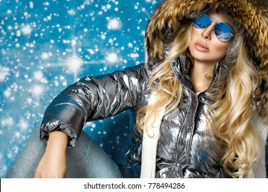 Beautiful stunning woman with long blond hair and perfect face dressed in winter clothing, silver warm jacket , sunglasses and cap on winter background