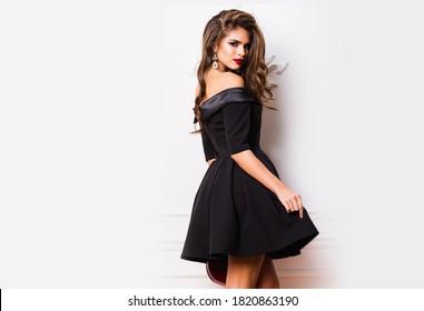 Beautiful stunning  woman with red full lips, smokey eyes make up , shining perfect  wavy hairs in  elegant casual black dress   posing on white background.