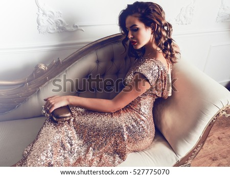 521dc57ca5 Beautiful stunning young lady in amazing glitter sequins dress sitting on  luxury armchair